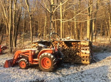 Wood pile and parked tractor